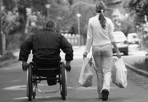 Na sliki je moški na invalidskem vozičku ob njem pa hodi ženska, ki nosi dve polni nakupovalni vrečki