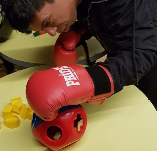 Udeleženec z rokavicami vstavlja like v žogo in tako spoznava težave z motoriko