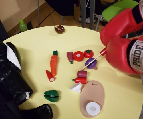 Udeleženec spoznava težave s fino motoriko z rezanjem lesene zelenjave v boksarskih rokavicah