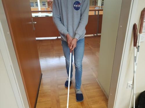 Hoja z belo palico po hodniku šole