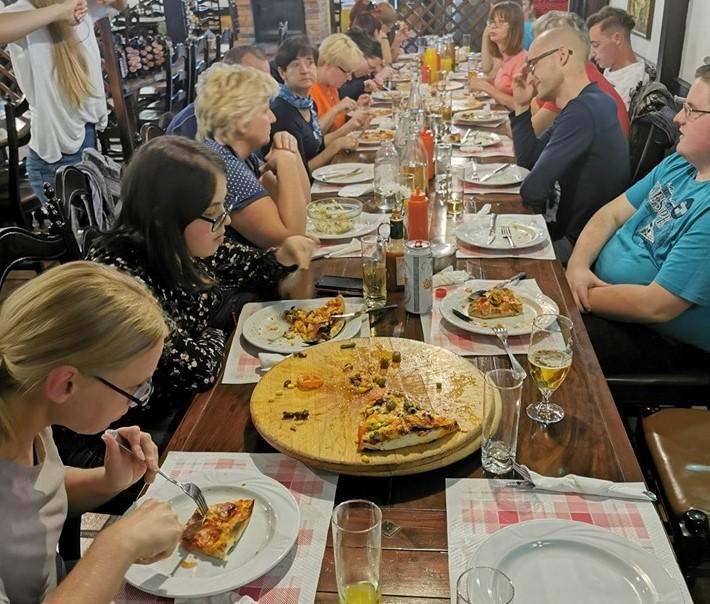 Člani in zaposleni DŠIS za veliko mizo jedo različne pice