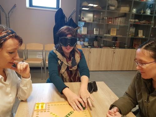 Udeleženke igrajo igro Človek ne jezi se prilagojeno za slepe in slabovidne