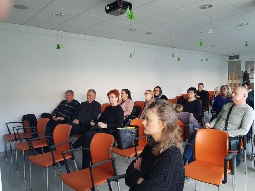 Udeleženci posveta sedijo na stolih in poslušajo predstavitev zaposlitvene rehabilitacije