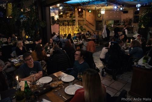 Udeleženci večerje se pogovarjajo za mizami