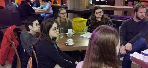 Predstavniki ŠOUM in DŠIS ter študenta, ki sta prejela laptopa sedijo ob pijači za mizo