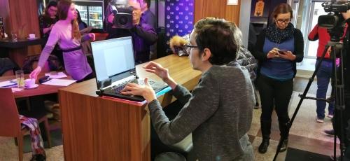 Študent prisotnim novinarjem prikazuje delo z novim računalnikom