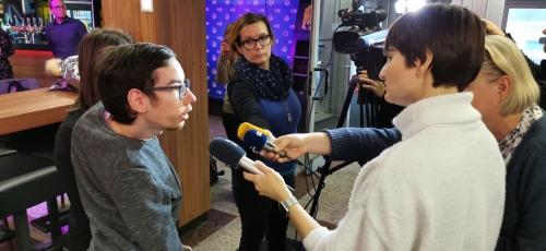 Študent odgovarja na vprašanja novinarjev
