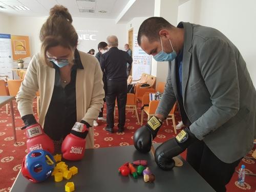 Udeleženka in udeleženec z boksarskimi rokavicami spoznavata kako je, če imamo težave s fino motoriko