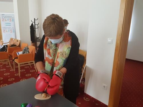 Udeleženka z boksarskimi rokavicami reže leseno gobo z lesenim nožem