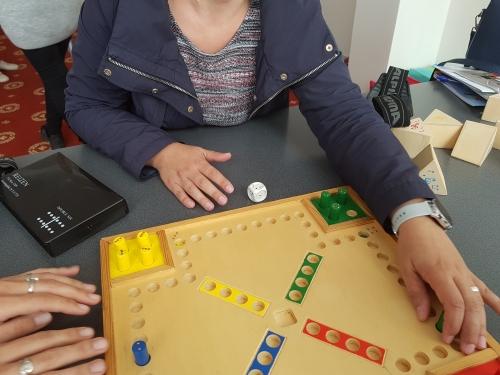 Udeleženka z rokami šteje polja na igrali ploskvi, da bo prestavila figuro na primerno mesto