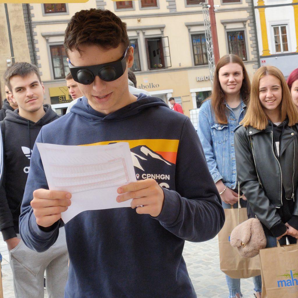 Dijak poskuša s simulacijskimi očali za tunelski vid brati avtobusni vozni red.