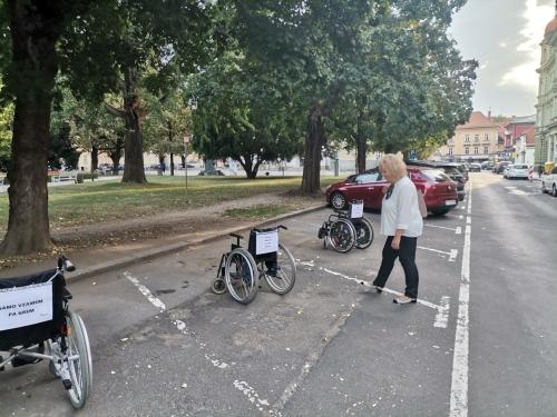 Invalidski vozički z napisi stojijo na parkiriščih